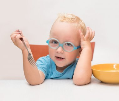 Baby boy with glasses sits at a table in front of a yellow plate