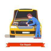 Mechanik opravář opravuje motor na auto čerpací stanice