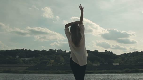 dívka stojí u řeky a vesele zvedá ruce