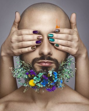 Man with creative makeup and flowers in his beard