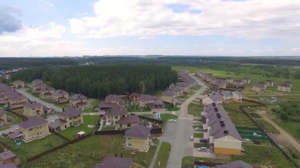 Aerial drone footage over the summer street. Modern luxury houses. Aerial flying over the residential area. Asphalt roads and sidewalks. Cloudy summer day