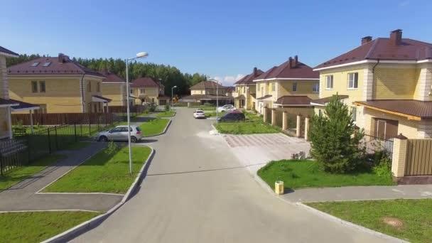 Drohnenaufnahmen aus der Luft über der Sommerstraße. Moderne Luxushäuser. Luftaufnahmen über dem Wohngebiet. Asphaltierte Straßen und Bürgersteige. Sonniger Sommertag. Die Kamera geht hoch