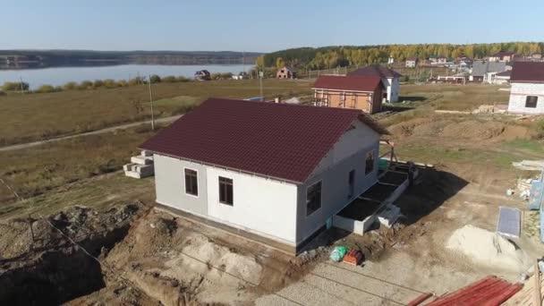 Létání po staveništi s nedokončeným moderním energeticky úsporným domem z pěnových bloků panelů se střechou s kovovými dlaždicemi. Dům ve vesnici u jezera. Slunečný den