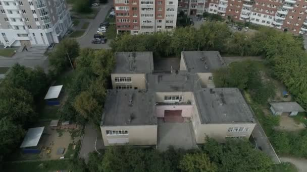 Aerial view of empty preschool building in residential area with Playgrounds Among trees and childrens drawings on the asphalt. Kindergarten in city with multi-storey buildings.