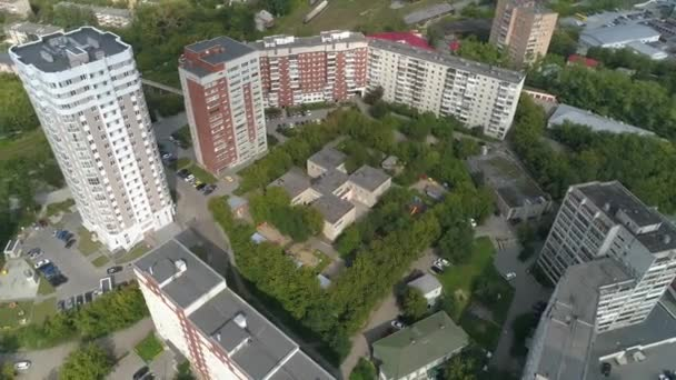 Aerial view of preschool building in residential area with Playgrounds Among trees and childrens drawings on the asphalt. Big city with multi-storey buildings. Near railway and trains