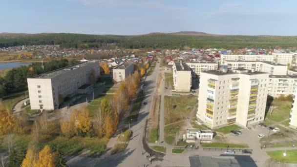 Letecký pohled na obytnou oblast s jednopatrovými domy v provinčním ruském městě. Na levé straně je nemocnice a rybník. Pětipodlažní a devítipatrové sovětské domy. Ve městě je mnoho stromů.
