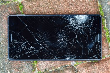 Broken mobile phone lying on pavement