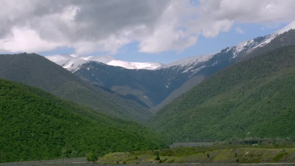 The Green Slopes Of The Mountains Snow Capped Peaks Dark River Flowing Below