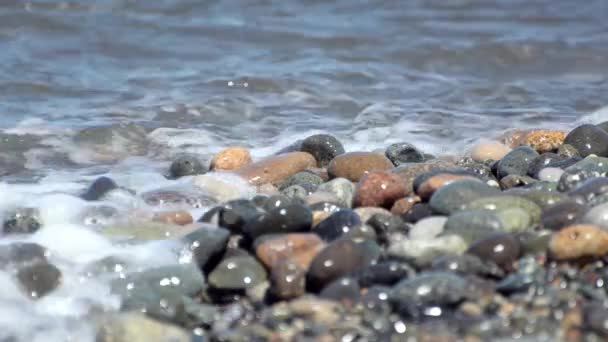 Sea waves beating against the large multi-colored pebbles. Close-up.