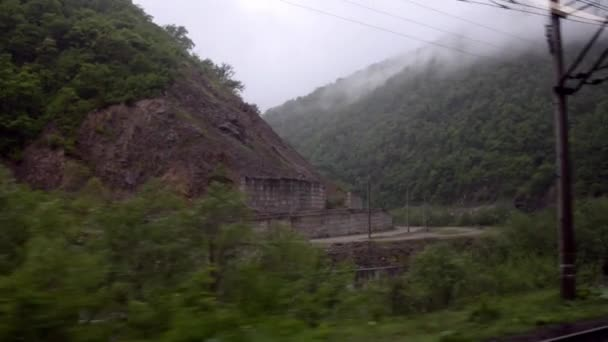The view from the train window at the mountain river and verdant hills in the fog. Caucasus, Georgia.