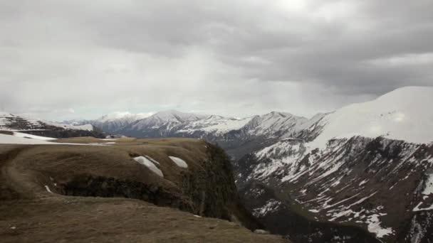 Na náhorní plošině pohled, údolí a zasněžené hory v pozadí husté temné mraky. Gruzie, Kavkaz