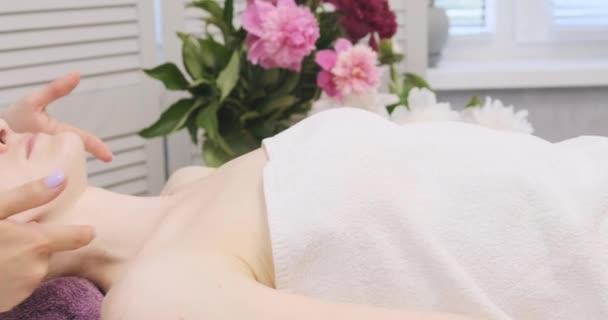 Mladá krásná žena na masáži obličeje v lázeňském salonu. Masér jemně dělá ženu modelující masáž obličeje.