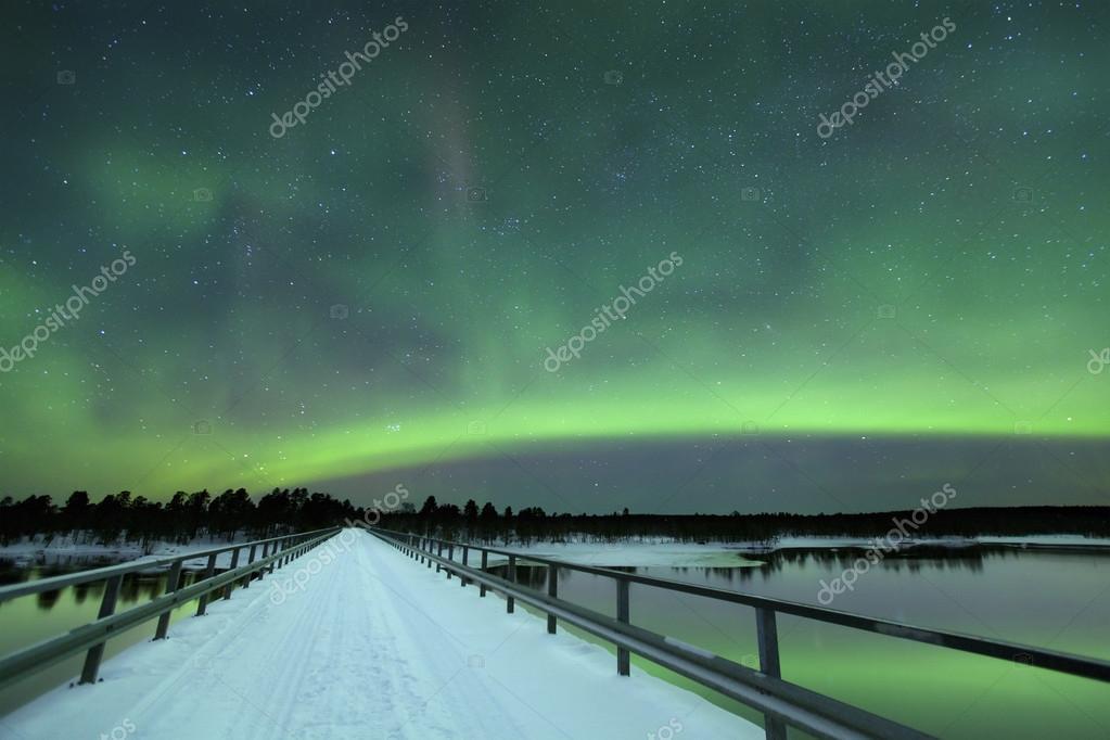 Aurora borealis over a bridge in winter, Finnish Lapland