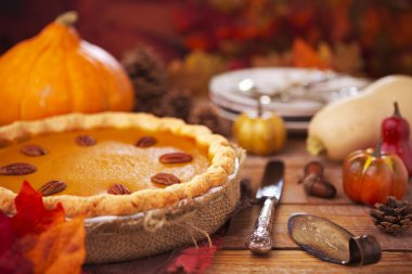 Homemade pumpkin pie on a rustic table with autumn decorations