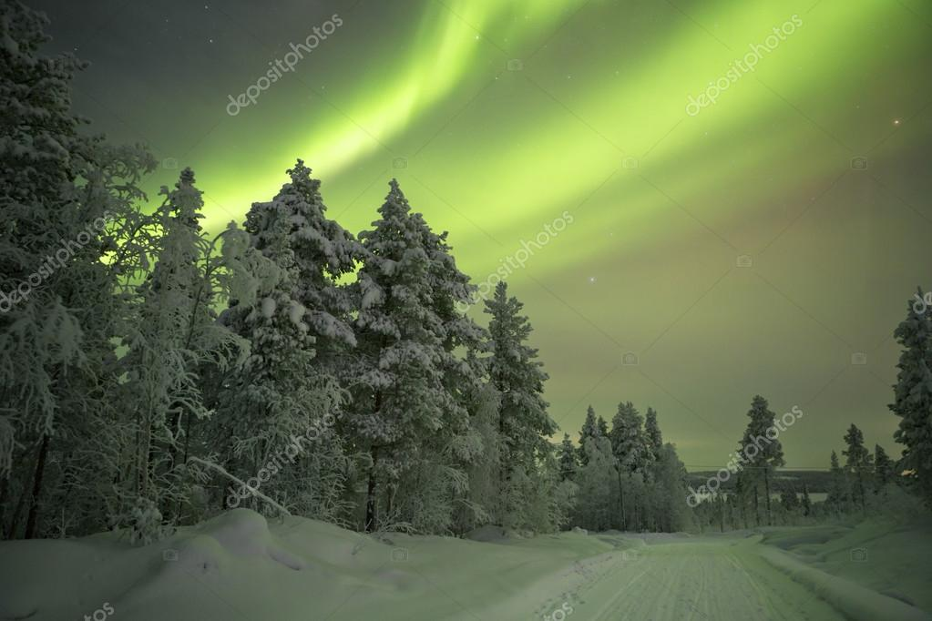 Aurora borealis over a track in winter, Finnish Lapland