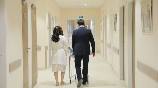 Young Family Walks Down The Hallway of the Hospital