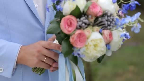 Svatební kytice v rukou ženicha