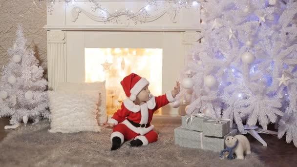 kleiner Weihnachtsmann sitzt unter einem Weihnachtsbaum mit Geschenken