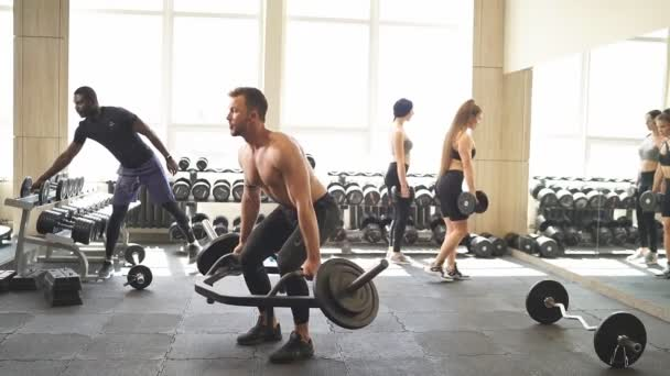 Shirtless young man doing heavy weight exercise for biceps