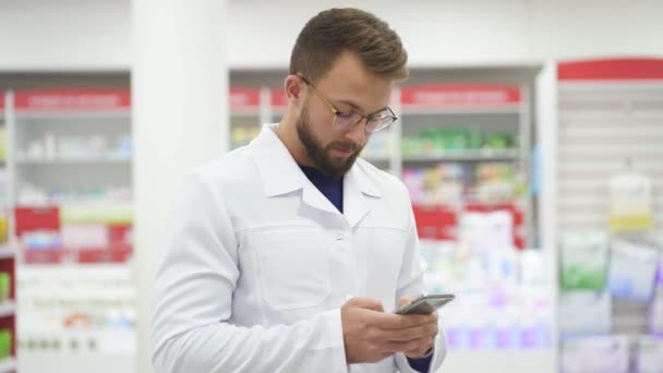 Young caucasian male pharmacist doctor in white medical uniform using smartphene