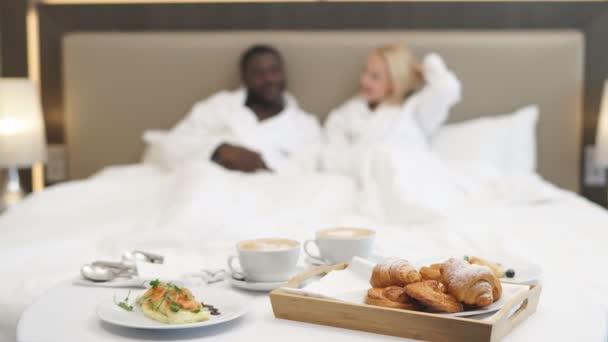 Detailní záběr na jídlo na misce, pár na posteli v pozadí.