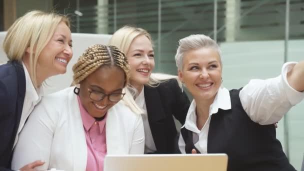 Portrét šťastné skupiny žen fotografujících na mobilním telefonu.