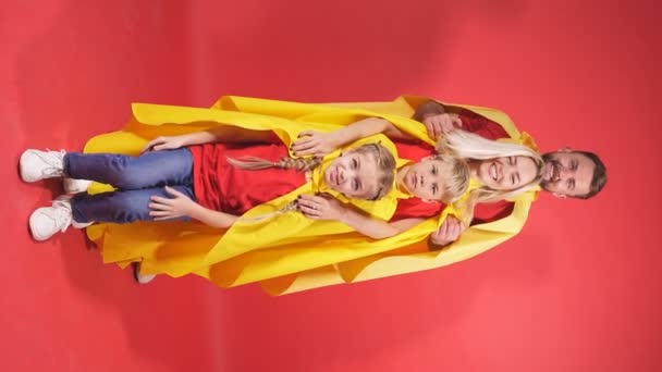Superfamilie in Mänteln steht isoliert auf rotem Hintergrund.