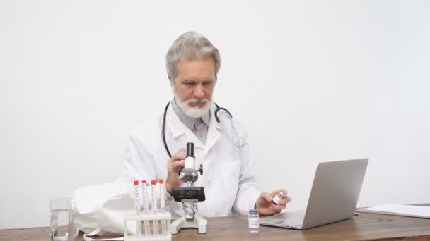 Senior male doctor examining, studying the coronavirus tests in tube
