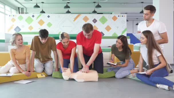 Group of people learning how to make first aid heart compressions with dummies during the training