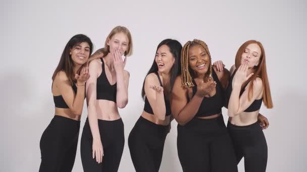 Vidám, többnemzetiségű, fekete sportos viseletű nők fúj csók a kamera előtt.