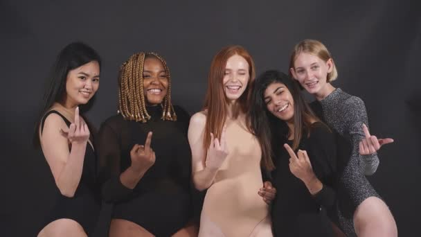 Portrait of careless caucasian african and asian women showing FUCK gesture.