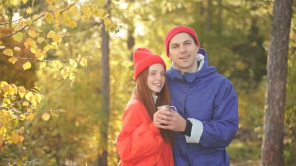 Portrait of a beautiful young caucasian couple standing in autumn forest and hugging