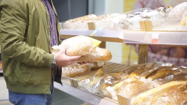 Portré fiatal kaukázusi férfi választott kenyeret szupermarketben