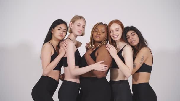 Vier schlanke Models und eine dicke Afrikanerin isoliert auf weiß.