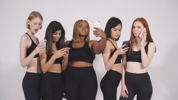 Emotional mixed race models using mobile phone posing at camera.