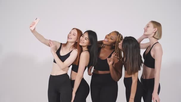 Portrait of cheerful diverse women taking selfie, looking at camera.