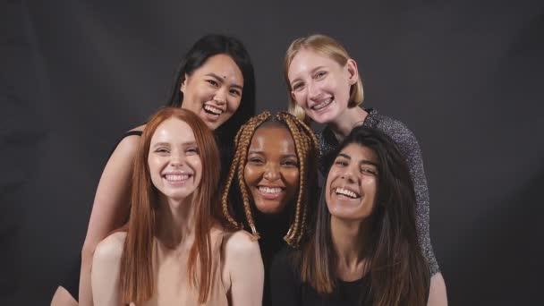 Porträt von fünf lächelnd lachenden schönen Frauen im Ganzkörperanzug, die zusammen stehen