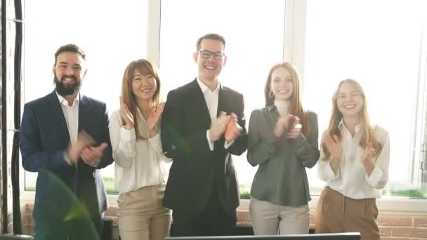 Mixed race team of business colleagues clapping hands and looking at camera, smiling.