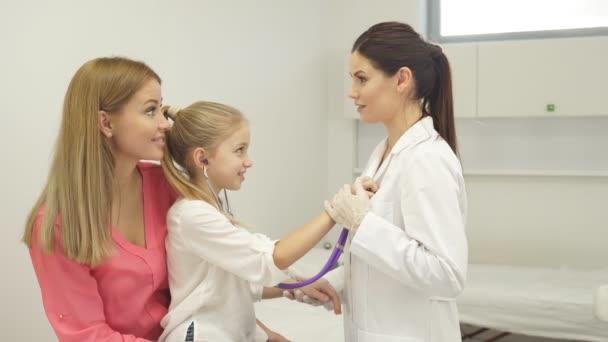 Fröhlich fleißiges Kindermädchen spielt mit Stethoskop im Krankenhaus