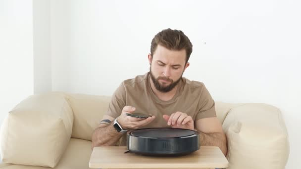 Young male using automatic smart robot vacuum cleaner working on floor