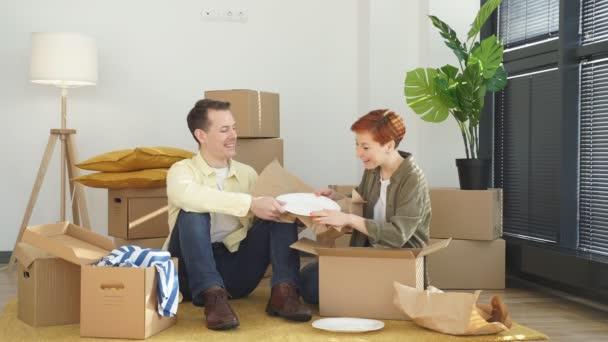 Veselý mladý ženatý pár kupující otevřít vybalit karton balíček nakupování on-line z domova
