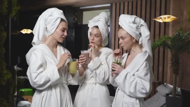 Drei junge Frauen trinken saftige Entgiftungssaftgetränke nach der Wellness-Behandlung, ruhen sich aus und genießen Schönheitsbehandlungen.
