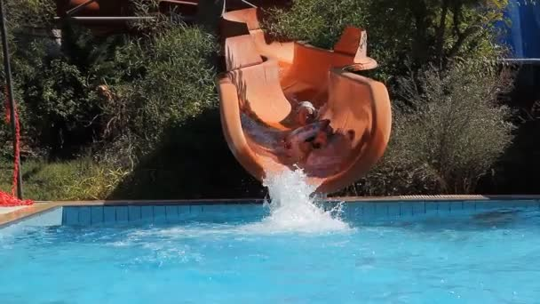 the boy rolls down the water slide