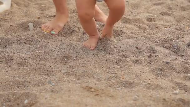 Baby první kroky na mořské pláži, detail