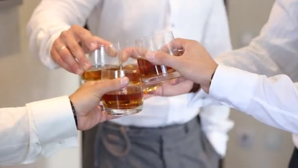 Men clinking whiskey glasses