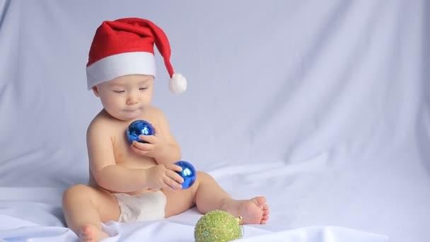 kleines Baby mit Weihnachtsmütze auf weißem Hintergrund