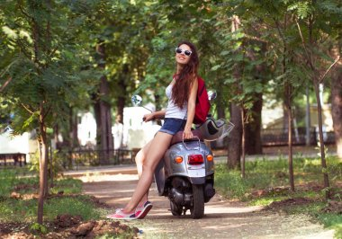 A beautiful young woman with sunglasses sitting on a scooter