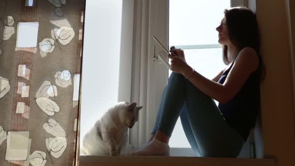Mladá žena s tabletu a kočka na okenní parapet
