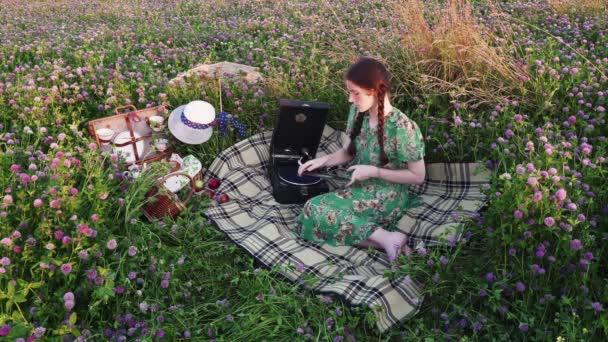 Mladá dívka na piknik vybere záznamy, klade na gramofon a poslouchat
