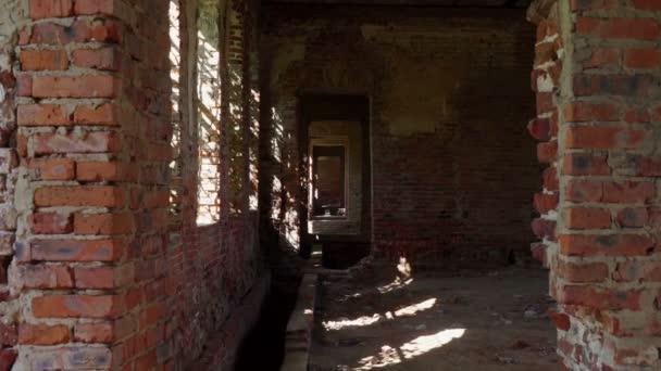 Blick durch Tür in engen Flur mit sonnenbeschienenen Flecken an kahler Steinwand.